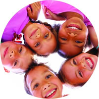 Five children in a huddle smiling down at camera | Fastrackids
